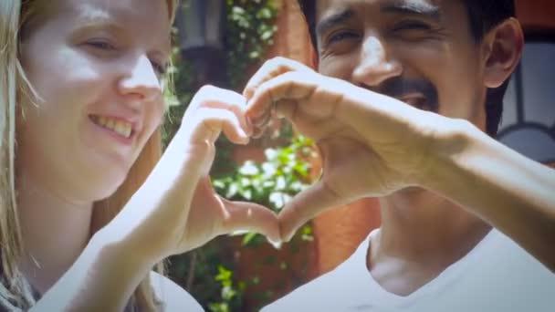Ein attraktives verliebtes Paar in den Zwanzigern macht mit seinen Händen ein Herz