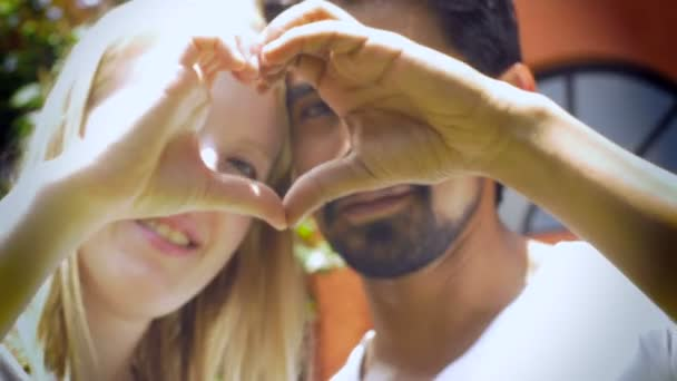 Ein attraktives Paar in Liebe Lächeln und ein Herz mit ihren Händen zu machen