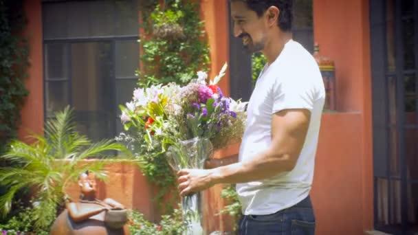 Ein attraktiver hispanischer Mann bringt Blumen zu einer jungen blonden Frau weit schuss