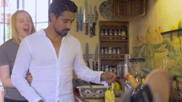 Glücklich junge interrassische Paar umarmen, während Mann kocht Frühstück