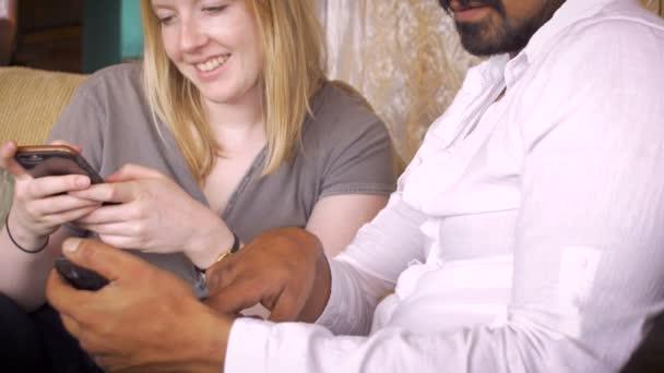 ein junges paar teilen technologie zusammen, während sie auf ihren telefonen surfen dolly shot