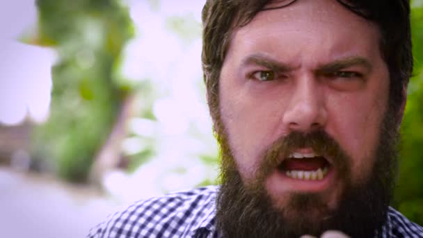 Dolly shot portrait of a bearded man giving the finger and shaking in anger