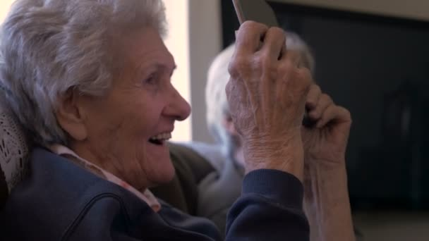 An older woman in her 90s looks at a digital tablet, laughing and smiling