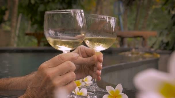 Nahaufnahme von zwei Gläser Weißwein in einem Pool, toast