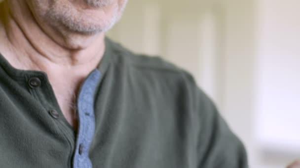 Ein älterer Mann füllt seinen wöchentlichen Tablettenspender wieder auf