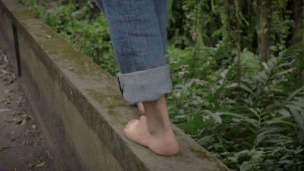 Bare feet walking and balancing on the edge of a bridge