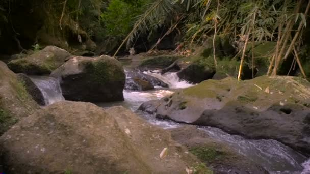 Slow pan of a rushing mountain river streaming down boulders in Bali