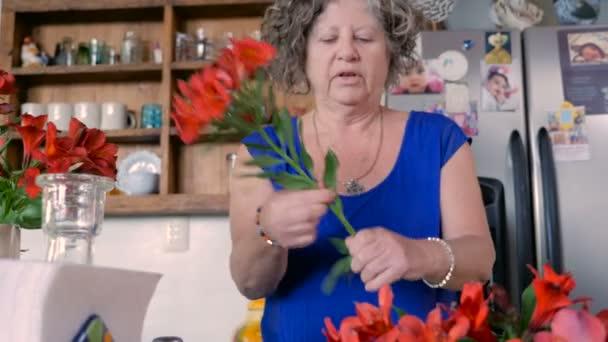 Žena v jejím 60s uspořádá čerstvých řezaných květin do vázy v kuchyni