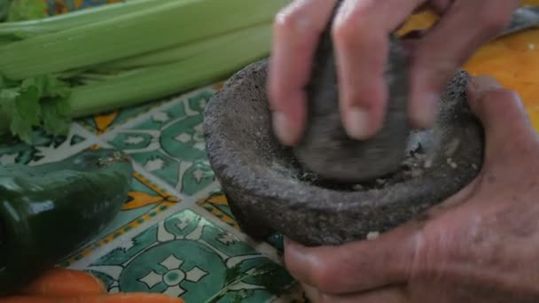 Close up push-in of a man grinding pepper with a mortar and pestle by hand