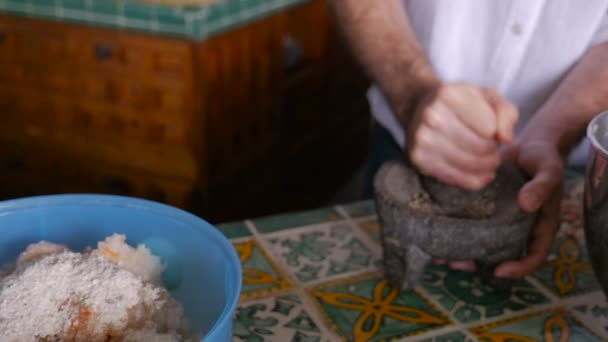 Slow motion of a man grinding pepper in a mortar and pestle