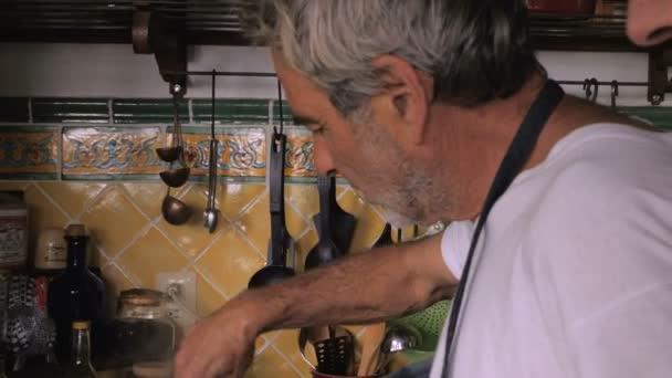 Starší muž a střední starší muž práce společně na rozpálený sporák
