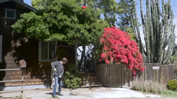 A man sweeps dead leaves from a driveway with a broom in front of a house