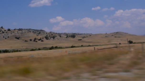Jízdy po venkovských Montana ukazující kopce s borovicemi a trávy