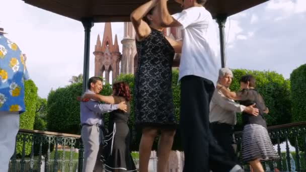 4 couples tango in el jardin with the parroquia in the background