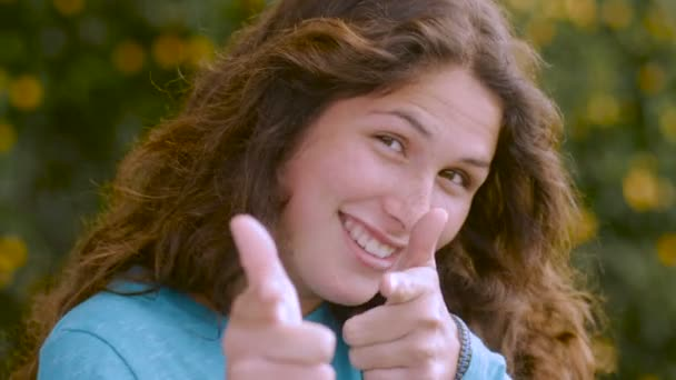 An young woman points with both hands at the camera and winks