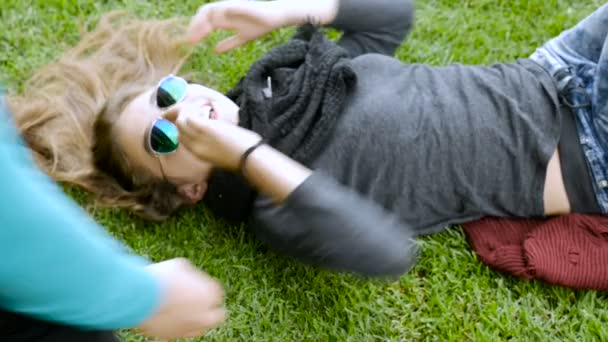 A young teenage girl is tickled and laughing while lying on the grass in slowmo
