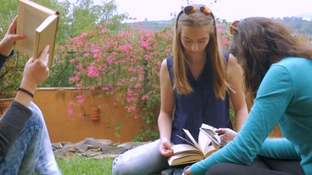 Three teen girls study outside while one reads her cell phone in slowmo