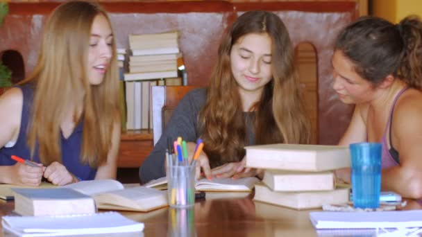 Teenage girls look for answers in books and then reference a tablet