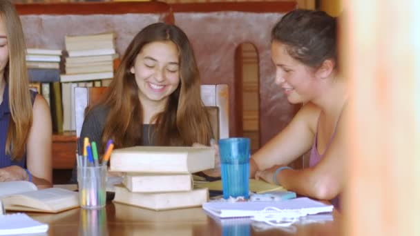 Three attractive teen girls studying with books together while one uses a tablet