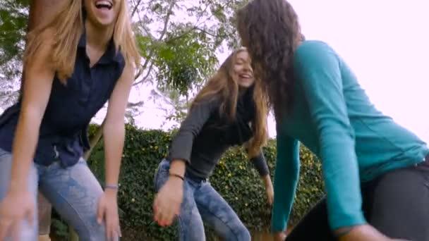Low angle handheld of attractive teenage girls dancing in slow mo
