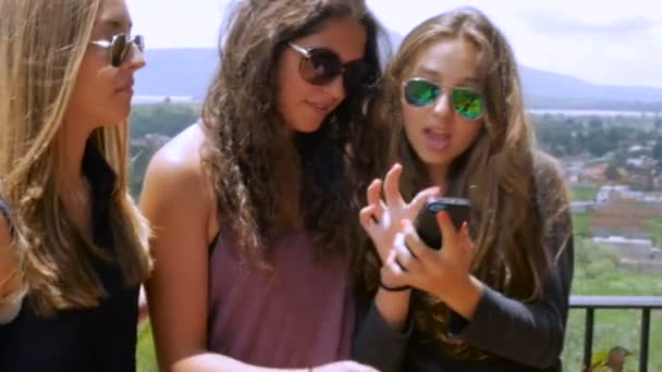 Three lovely teenage girls look at their smart phone together in slowmo
