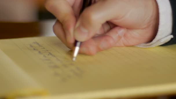 Businessman hand writing letter in legal notebook with pen CLOSE UP
