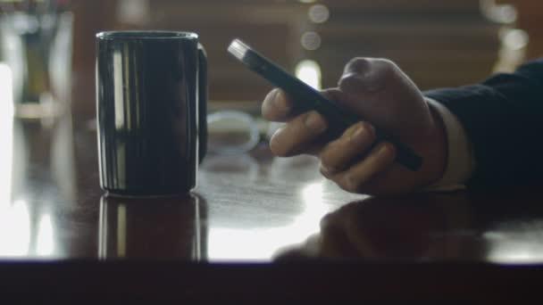 Man scrollt durch seine Smartphone während in einem Kaffeehaus in der Nacht