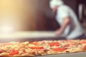 Fotografia Panettiere del cuoco in uniforme nera, mettendo la pizza nel forno con pala a cucina del ristorante