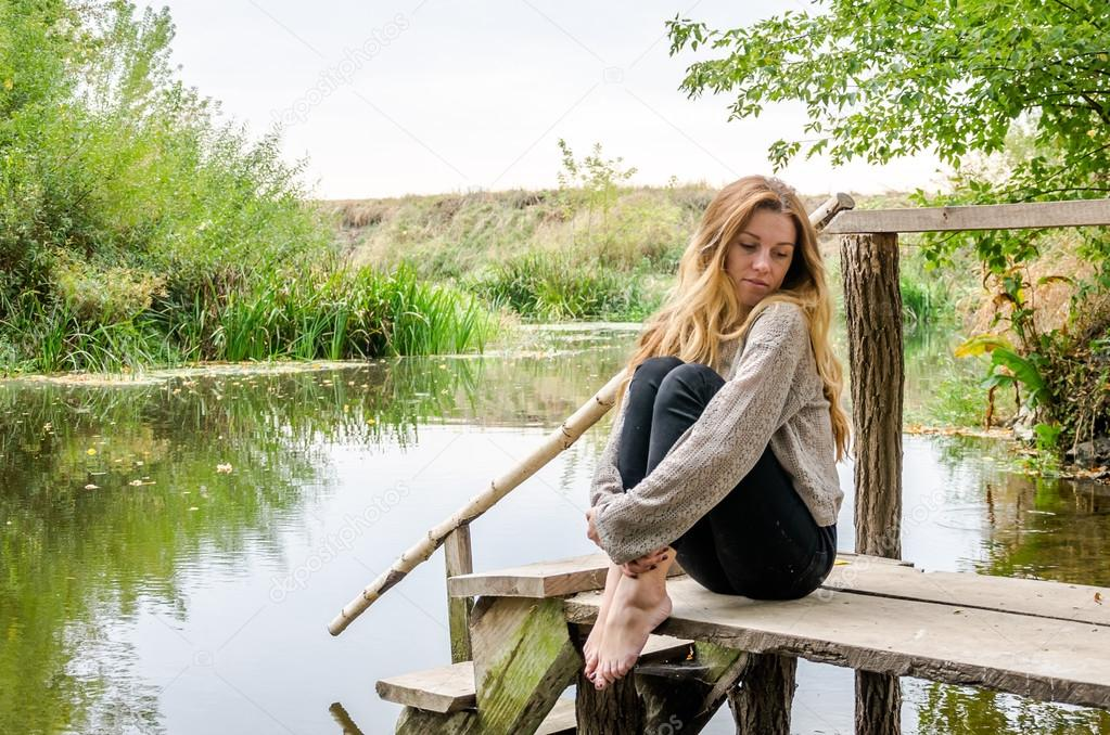 Young beautiful woman model with long blond hair sitting with different emotions laughter, sadness, sorrow, thoughtfulness on a wooden bridge on the bank of the river and the forest looking for water