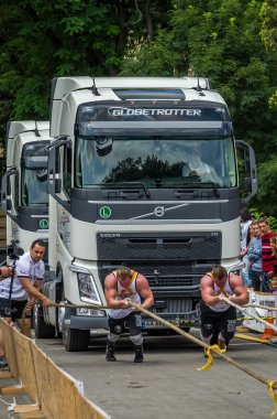 LVIV, UKRAINE - JULY 2016: Two strong athlete bodybuilder strongman pulling with ropes two huge truck in front of enthusiastic audiences