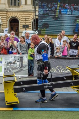 LVIV, UKRAINE - JULY 2016: Strong athlete bodybuilder strongman carries heavy metal design competitions World Strongest Team before enthusiastic audiences