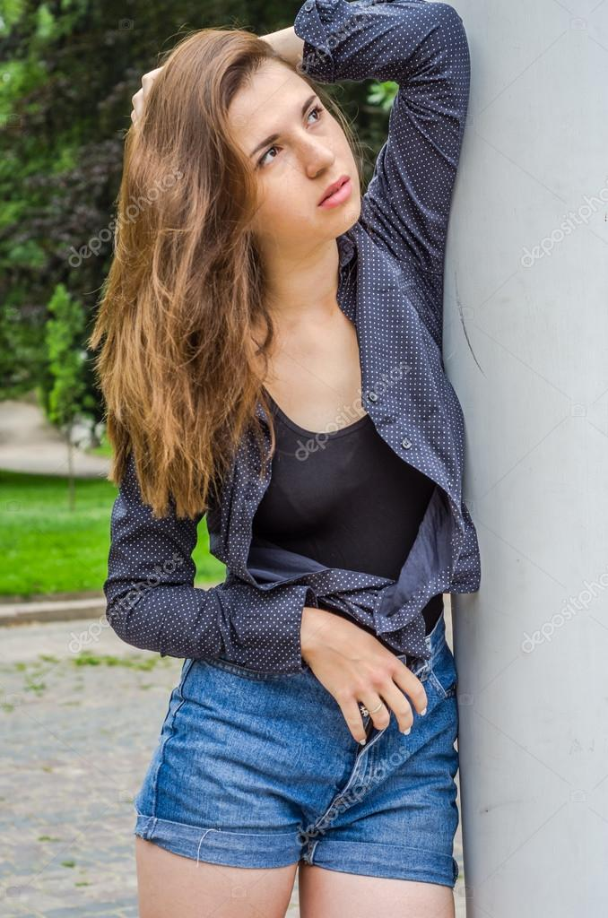 Young cute girl with long hair in a shirt and denim shorts