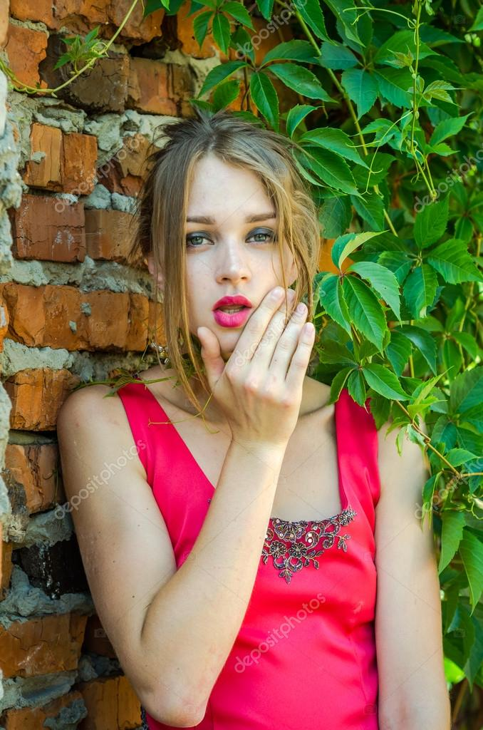 Young charming blonde girl with long hair and beautiful eyes with a sad look face leaned against - Charming teenage girls image ...