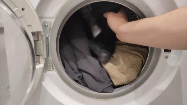 A házvezetőnő szennyest pakol a mosógépbe.