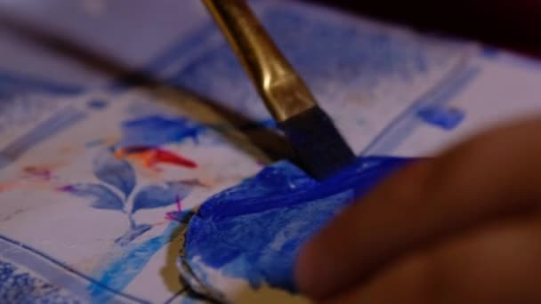 Close up of the little hand of a kid painting with watercolors