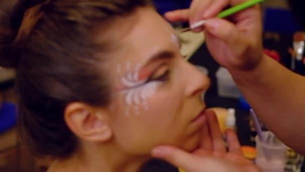 Egy profi művész, aki egy modell arcát festi.