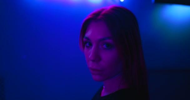Junge Frau in Neonlicht trägt futuristische Brille. Es gibt eine Wirkung von Lärm, Getreide.