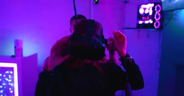 Zaměstnanec VR klubu pomáhá odstranit gadget z hlavy mladých žen. Je tu hluk, obilí..