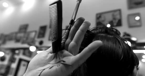 Barber performs a haircut in a barbershop. Black and white video. Bottom view.
