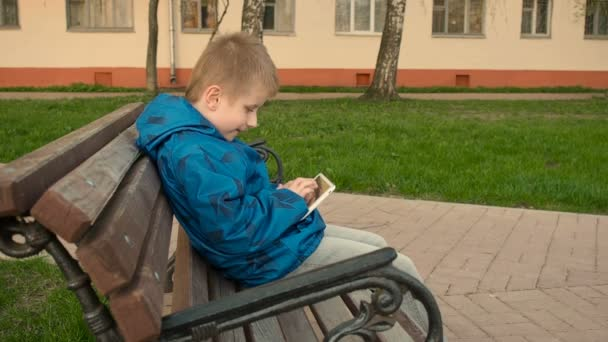 boy uses tablet pc outdoors in the park