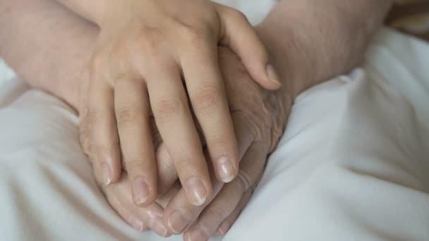 Una giovane femmina mani confortante unanziana coppia di mani di donne anziane