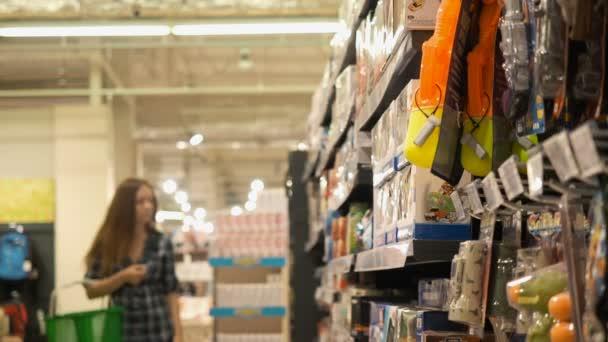 Mladá krásná žena zvolí hračky v supermarketu
