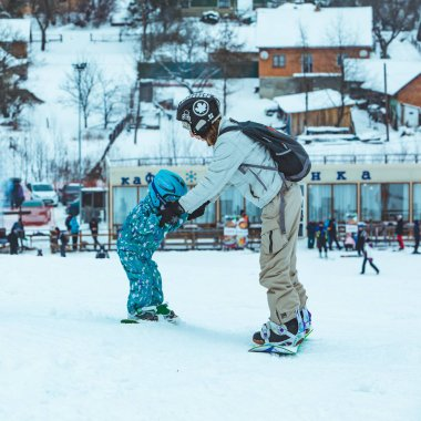 LVIV, UKRAINE - January 12, 2019: mother teaching little girl to snowboarding. lifestyle. winter activities