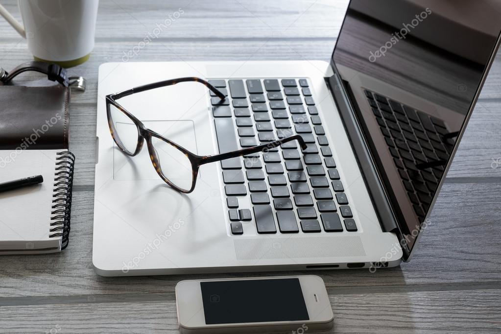 52e99f0667bad1 Computer bril en een witte telefoon op het Bureau wit — Foto van  aleksandrkorotun