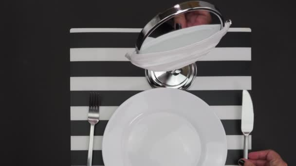 Social distancing restaurant single dining behaviour concept. Female sets a dish at a table on eating alone before a mirror with covid-19 protection mask, encouraging safety guidelines practices.