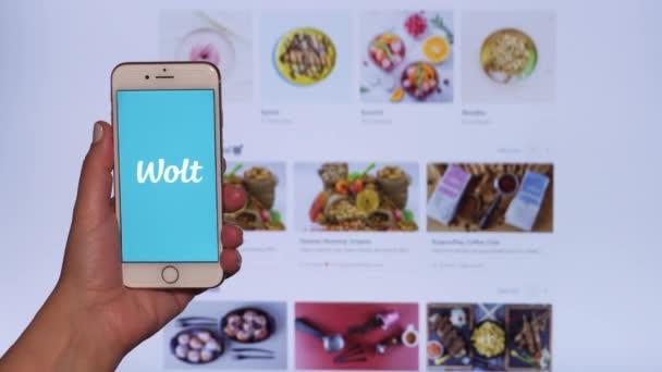 Wolt Essenslieferungskonzept. Weibliche Hand hält vor dem Bildschirm Handy mit finnischem Firmenlogo und scrollt eine Webseite mit Plattform-Restaurant-Partnern.