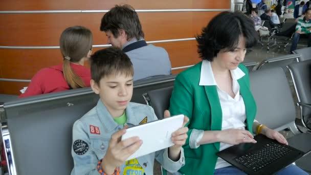 moskau, russland, 26. mai 2016. junge frau und kind sitzen im flughafen terminal, warten auf abflug und spielen auf dem tablet