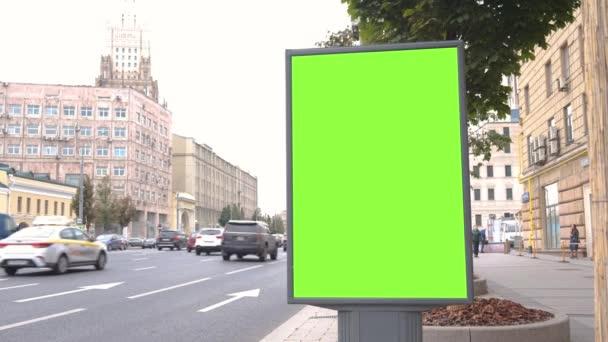 Plakatwand mit grünem Bildschirm befindet sich auf einer belebten Straße. Autos bewegen sich mit hoher Geschwindigkeit