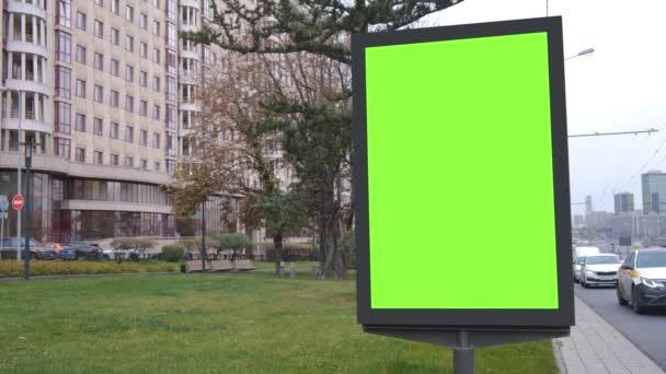 Zelený billboard umístěný vedle zeleného trávníku a velké budovy