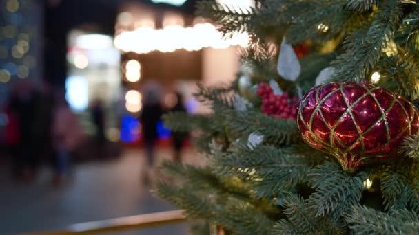 Velký červený míč, ozdoba vánočního stromečku. Krásná pouliční světla rozostřená